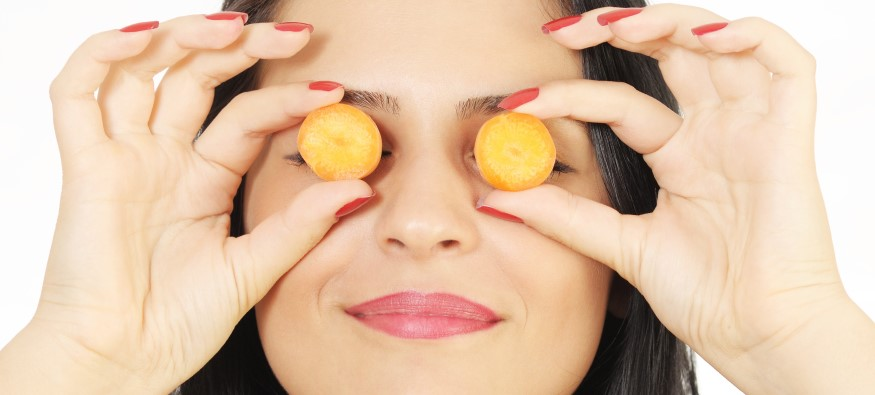 woman holding carrot slices over eyes